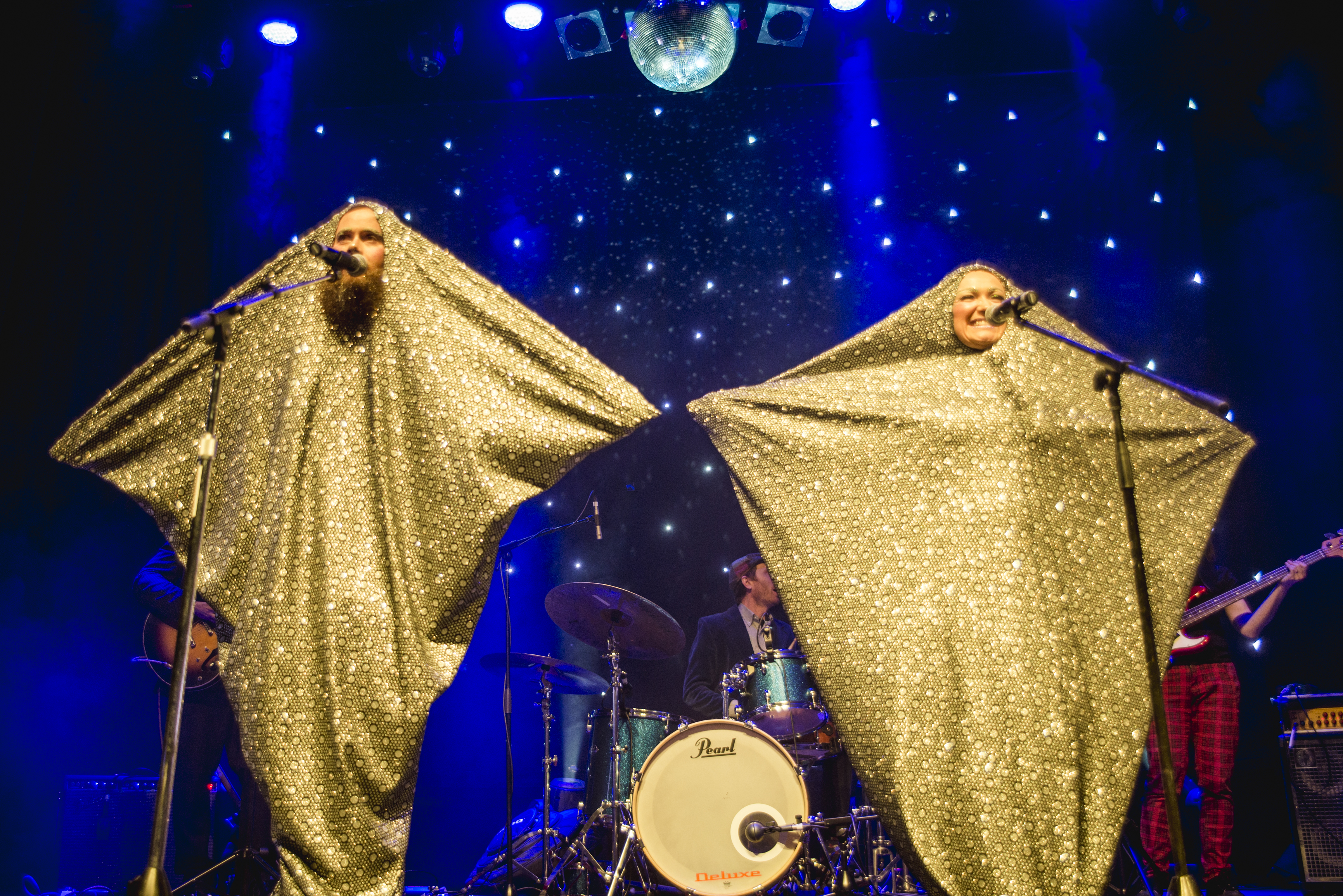 Two performers dressing as stars in golden costumes, each standing behind a microphone on the stage
