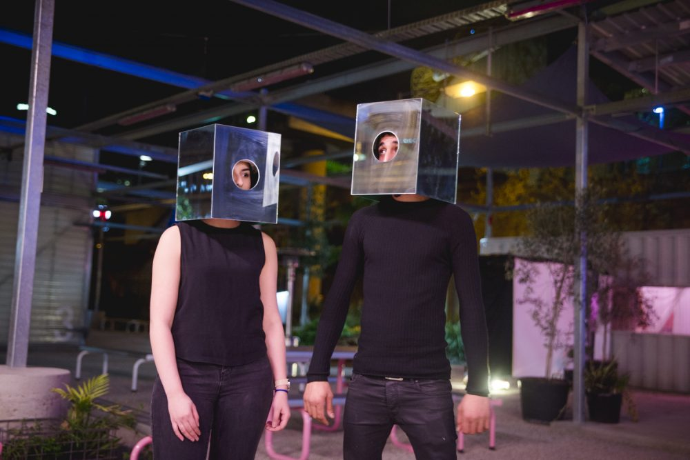 Two performers wearing metal box on their heads, starring at each other in an outdoor space