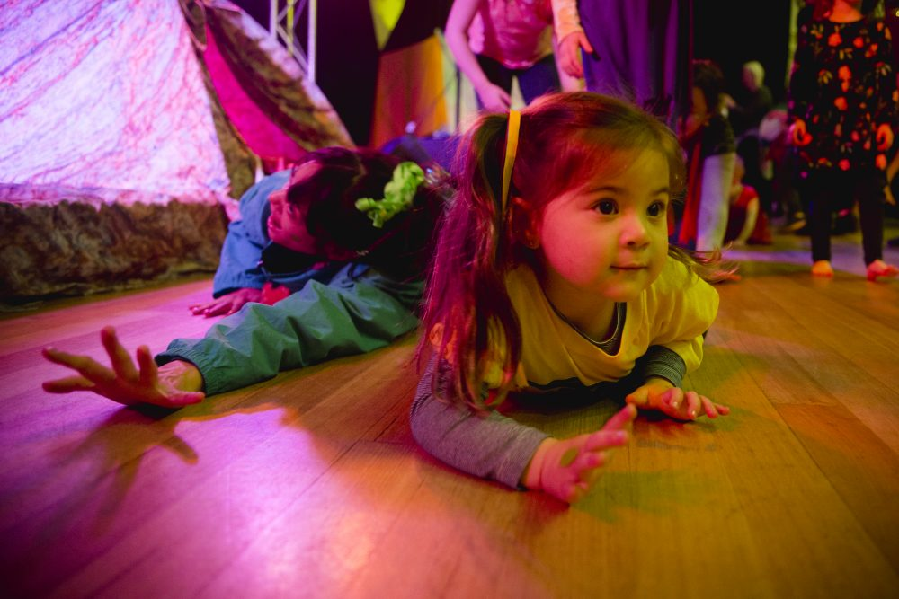a kid crawling on the floor in a performing space